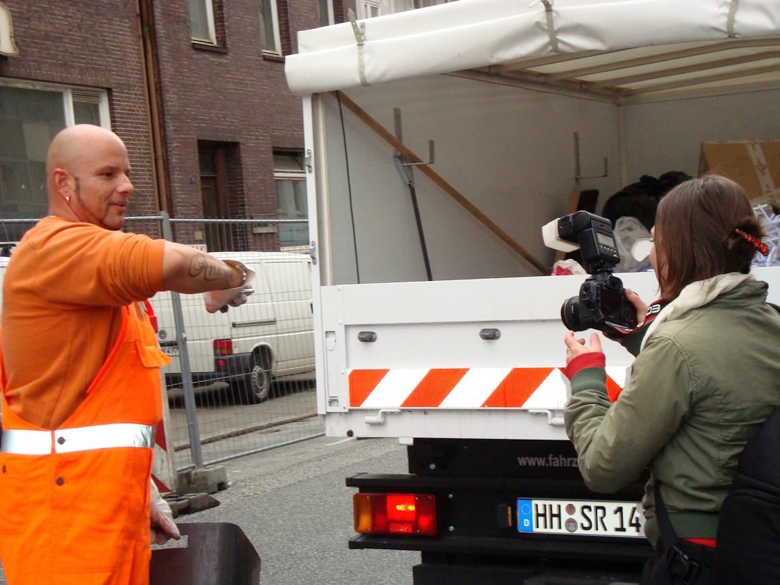 """Das Bild zeigt Anne Oschatz beim Fotografieren von Robert Szwejk,dem """"Kümmerer"""" vom Hansaplatz. Aufgenommen am 07.05.2010 um  15:32 Uhr von Christiane Schuller.Er hält seinen Arm in die Kamera um sein Tatoo zu zeigen."""