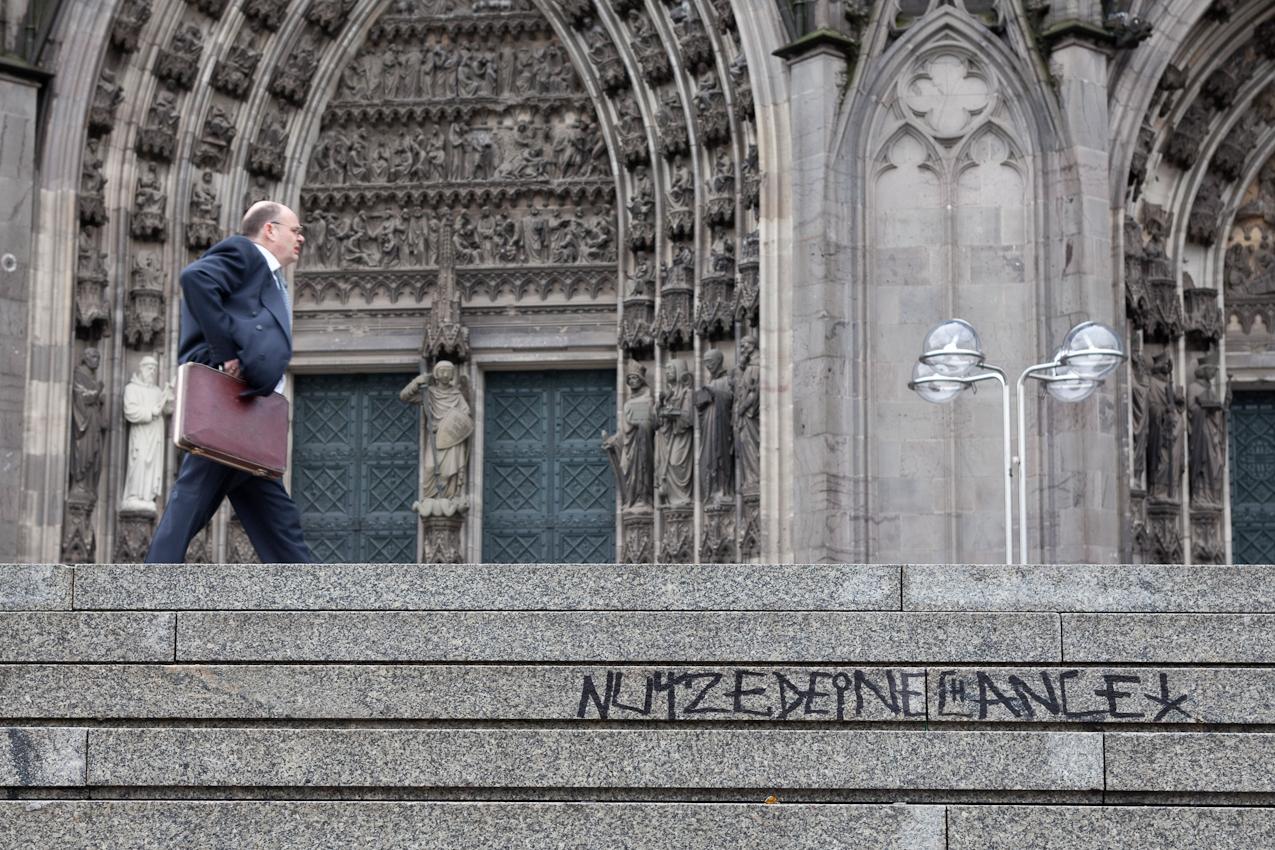 """Graffiti """"Nutze deine Chance"""" an der großen Freitreppe vom Bahnhof zur Domplatte. Passant mit Aktentasche."""