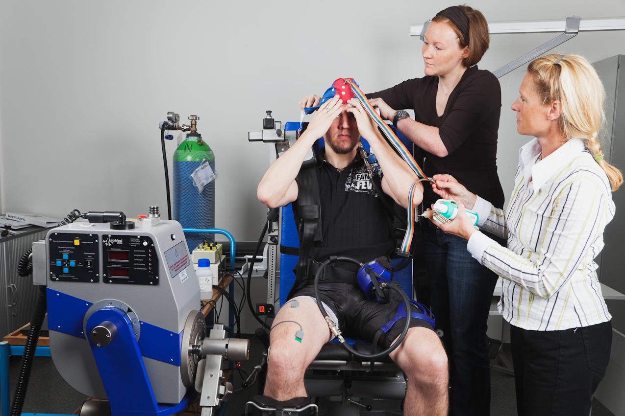 Fotografin Gaby Wojciech, Making-Of. An der Deutschen Sporthochschule Köln werden im Institut für Bewegungs- und Neurowissenschaften die Muskel- und Gehirnaktivitäten unter Sauerstoffmangel bei Krafttraining erforscht. Der Proband Fabian Schürg (links) sitzt auf einer elektronisch gesteuerten Kraftmaschine.  Die Wissenschaftlerin Vera Brümmer (mitte) zieht dem Proband die EEG-Kappe auf, welche die Hirnströme aufzeichnet. Die Fotografin Gaby Wojciech (rechts im Bild) unterstützt sie dabei. Das Bild wurde am 07.05.2010 um 10.13 Uhr vom Laborleiter Dr. Axel Knicker aufgenommen.